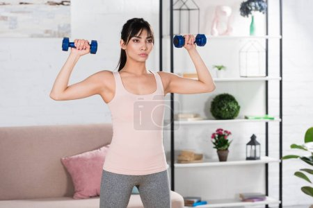 attractive young woman doing exercise with dumbbells at home