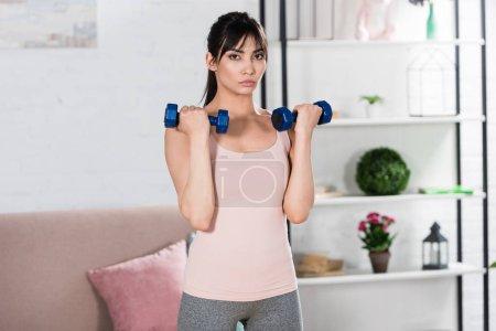 Photo pour Fit la jeune femme de faire des exercices avec des haltères à la maison - image libre de droit