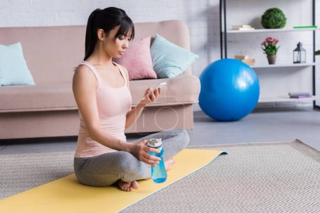 beautiful young woman relaxing on yoga mat after workout and using smartphone at home