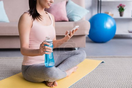 cropped shot of young woman relaxing on yoga mat after workout and using smartphone at home