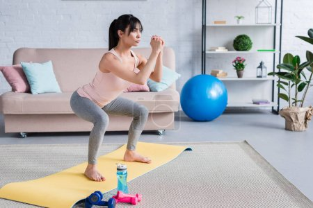 Photo for Fit young woman doing squats on yoga mat at home - Royalty Free Image