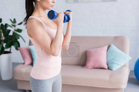 cropped shot of young woman working out with dumbbells at home