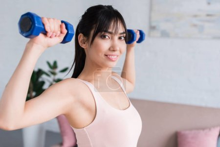 happy young woman working out with dumbbells at home and looking at camera