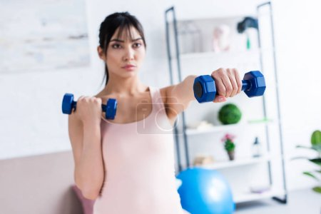 athletic young woman working out with dumbbells at home