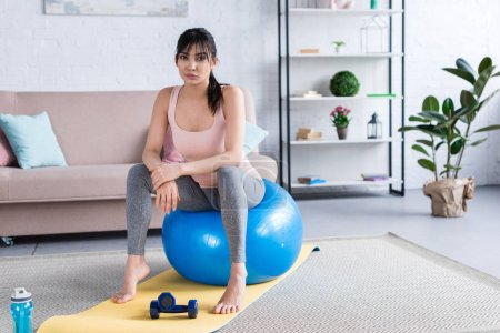sporty young woman sitting on fit ball after workout at home