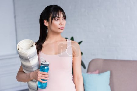 beautiful young woman with rolled yoga mat and bottle of water at home
