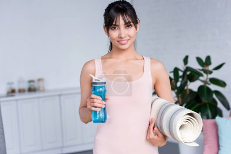 happy young woman with rolled yoga mat and bottle of water at home