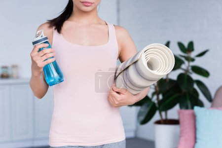 cropped shot of young woman with rolled yoga mat and bottle of water at home