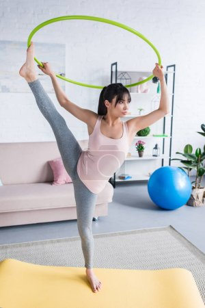 sporty young woman demonstrating her flexibility with hula hoop at home
