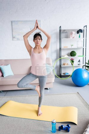 attractive young woman practicing yoga in Tree pose (Vrksasana) at home