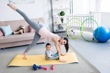 young mother practicing yoga in One Legged Downward-Facing Dog pose while her little child sitting on mat at home