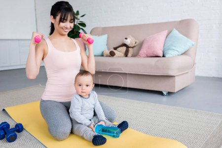 young smiling mother working out on yoga mat with her little child at home