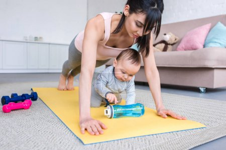 young sporty mother doing plank exercise on yoga mat with her child at home