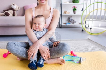 cropped shot of young sportive mother and happy child sitting on yoga mat at home