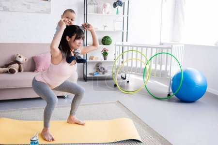Photo for Young sportive mother carrying her little child on shoulders while doing squats - Royalty Free Image