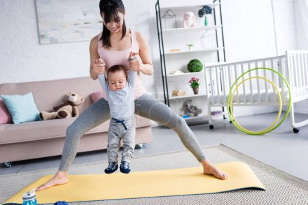 young sporty mother carrying little child while standing on yoga mat at home