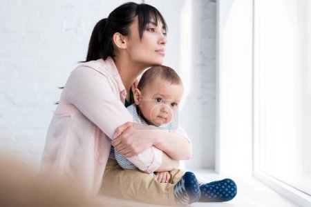 young beautiful mother embracing her little child while he sitting on windowsill and looking through window