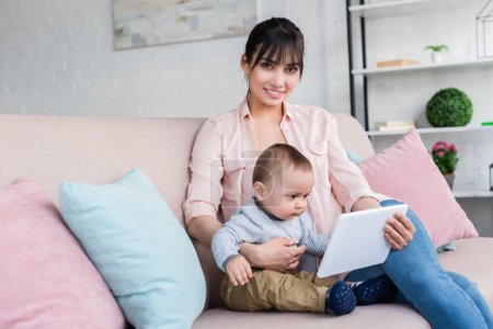 young beautiful mother and little child with tablet sitting on couch at home