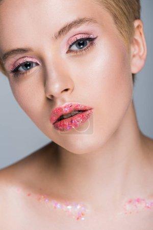 Photo pour Jolie femme avec des paillettes sur les lèvres en regardant caméra isolée sur fond gris - image libre de droit