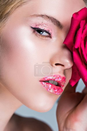 attractive woman with glitter on lips touching face with red rose