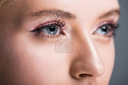 close up of attractive woman with sparkling makeup looking away