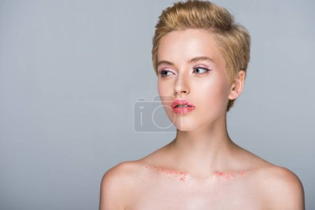beautiful woman with glittering makeup and short haircut looking away isolated on grey