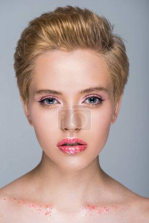 Foto de Mujer atractiva con maquillaje brillante y corte de pelo corto mirando a cámara aislada en gris - Imagen libre de derechos