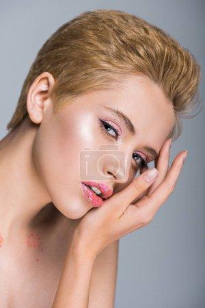 Foto de Mujer atractiva con brillo en los labios, tocarse la cara y mirando a cámara aislada en gris - Imagen libre de derechos