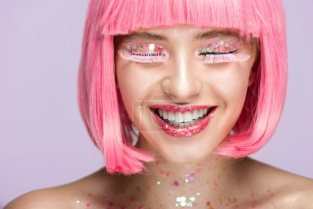 smiling attractive woman with pink hair, glittering makeup and long eyelashes isolated on violet