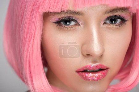Foto de Mujer atractiva con maquillaje brillante mirando a cámara y rosa - Imagen libre de derechos