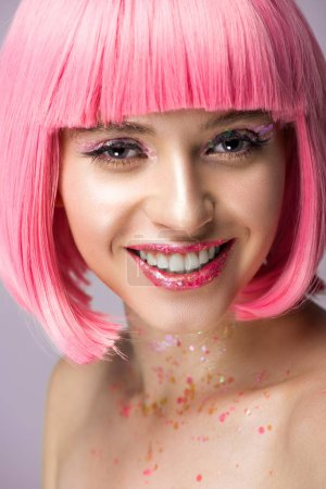 smiling attractive woman with pink hair and makeup with glitter looking at camera isolated on violet