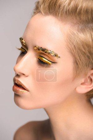 Photo pour Vue de côté d'une femme attirante avec des paillettes or sur visage isolé sur fond gris - image libre de droit