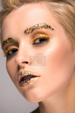 headshot of attractive woman with glittering makeup looking at camera