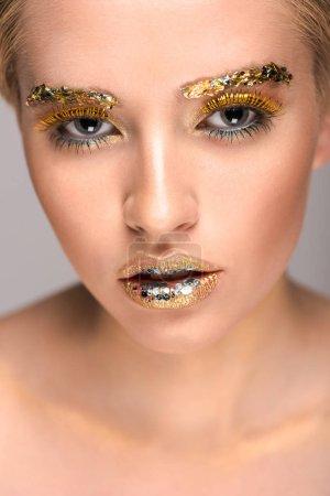 Photo pour Jolie femme avec des paillettes dorées sur le visage en regardant la caméra - image libre de droit