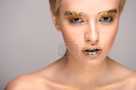 attractive woman with golden glitter on face looking at camera isolated on grey
