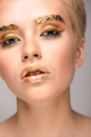 attractive stylish woman with golden glitter on face looking at camera isolated on grey