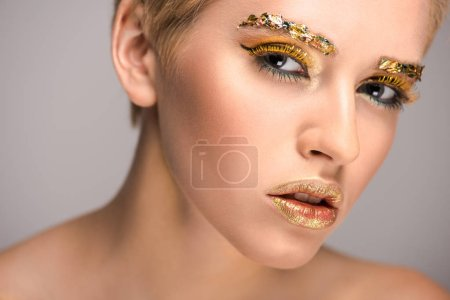 Foto de Mujer atractiva con purpurina oro glosa en la cara mirando a cámara aislada en gris - Imagen libre de derechos