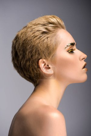 side view of attractive woman with golden glitter on face and short hair isolated on grey