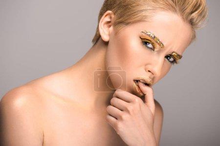 Foto de Mujer atractiva con brillo dorado en la cara, morder pulgar aislado en gris - Imagen libre de derechos