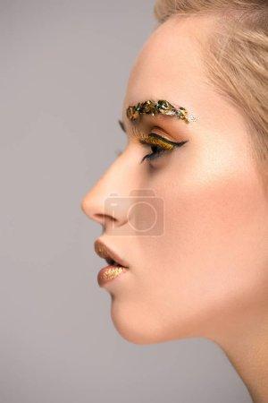 Foto de Vista lateral de una mujer atractiva con maquillaje brillante dorado aislado en gris - Imagen libre de derechos