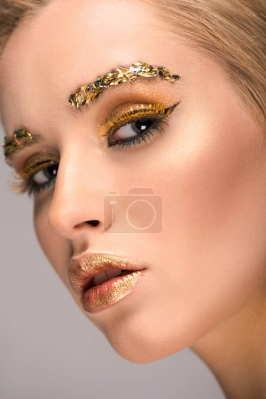 headshot of attractive woman with golden glittering makeup looking at camera isolated on grey