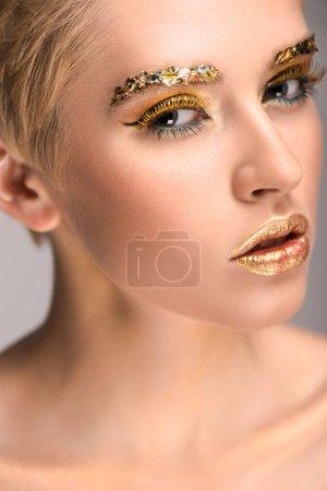 Photo pour Jolie femme blanche avec des paillettes dorées sur le visage en regardant la caméra - image libre de droit