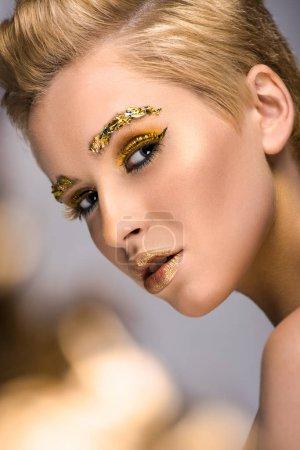 Photo pour Jolie femme avec des paillettes dorées sur le visage et coupe de cheveux court isolé sur fond gris - image libre de droit
