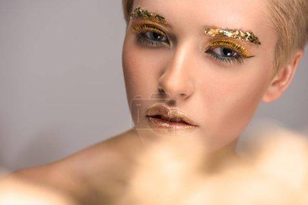 Photo pour Belle femme avec golden paillettes brillantes sur visage regardant caméra isolée sur fond gris - image libre de droit