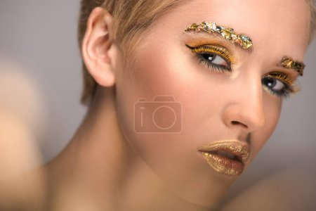 Photo for Attractive woman with colored bright glitter on face looking at camera isolated on grey - Royalty Free Image