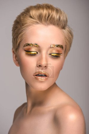 beautiful girl with golden shiny makeup looking down isolated on grey