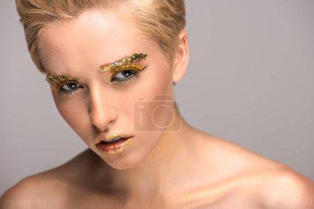 Foto de Mujer irritada atractiva con maquillaje brillante dorado aislado en gris - Imagen libre de derechos