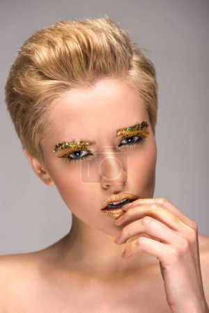 attractive woman with golden glitter on face touching lips and looking at camera isolated on grey