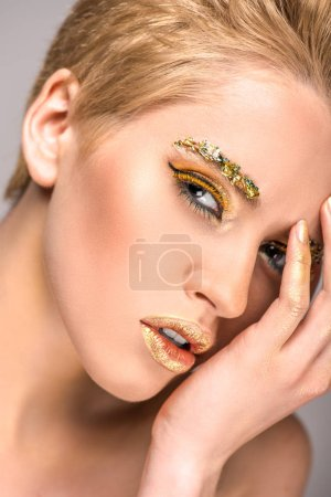 attractive woman with golden bright makeup touching face and looking at camera isolated on grey