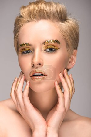 attractive woman with golden bright makeup touching face isolated on grey